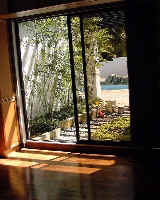 Water view from 2nd bedroom. Potted plants enhance tranquility of house.